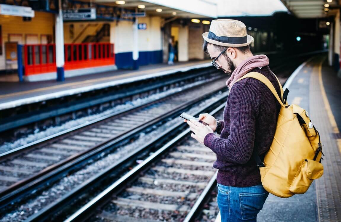 Homem usando o celular em estação de trem